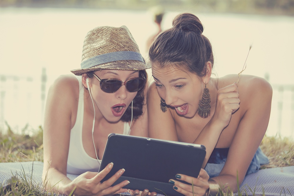 Closeup portrait two surprised girls looking at pad discussing latest gossip news. Young shocked funny women friends reading sharing social media news on mobile pad computer outdoors in park