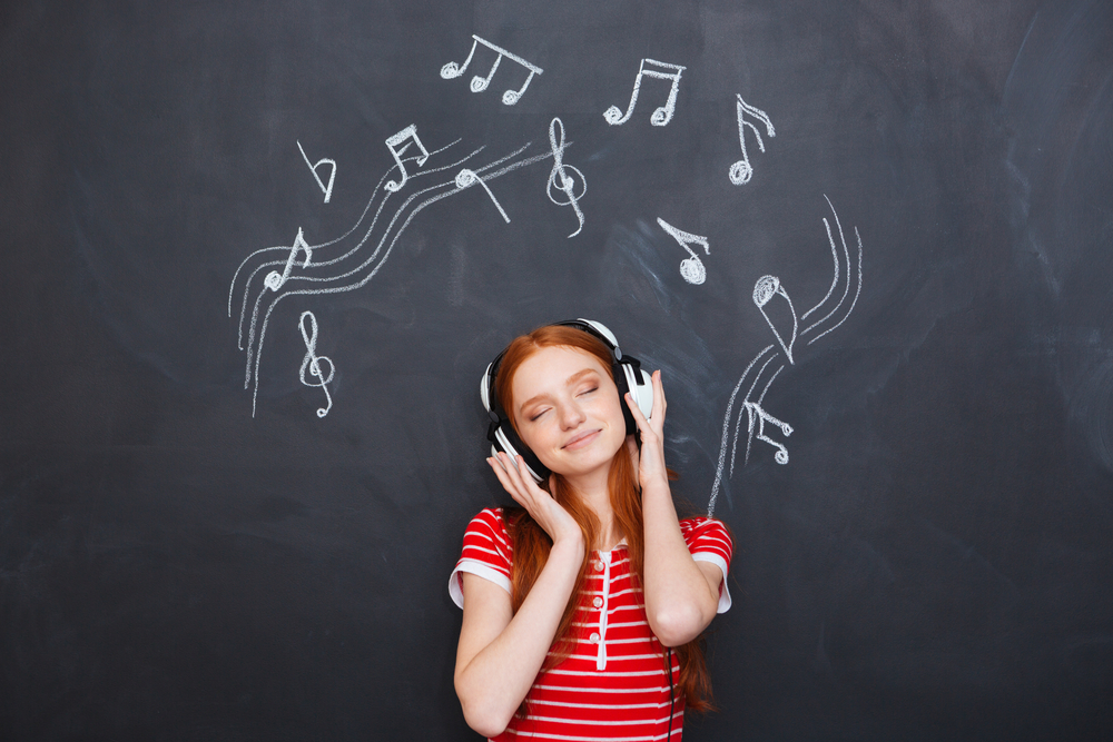 Relaxed smiling beautiful young woman listening to music in headphones over chalkboard background